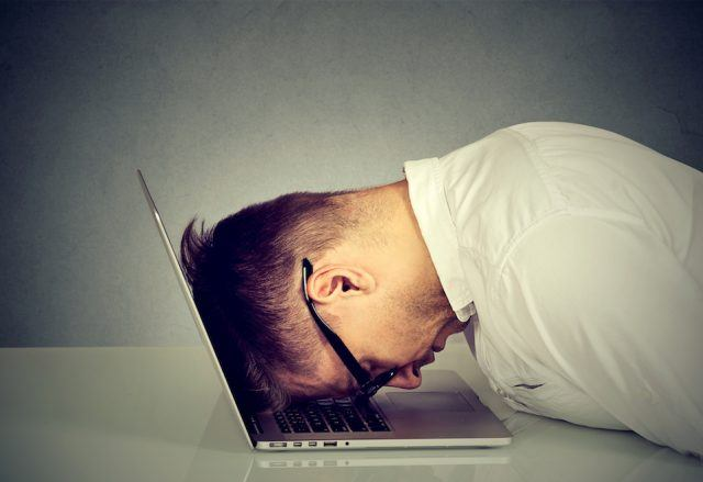 man banging head on laptop