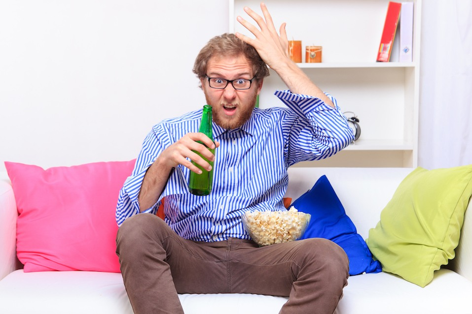 man yelling at his tv with popcorn and a beer