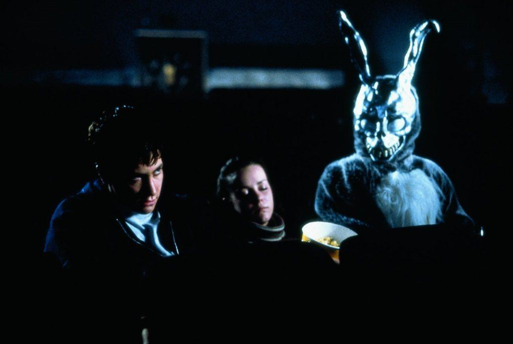 Donnie Darko (Jake Gyllenhaal), Gretchen (Jena Malone), and a person dressed as an evil-looking rabbit sit in a darkened movie theater.