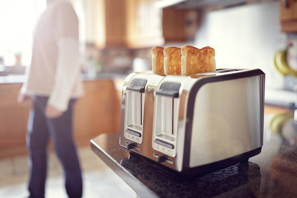 Early morning toasted bread, man in the kitchen preparing toast for breakfast at sunrise