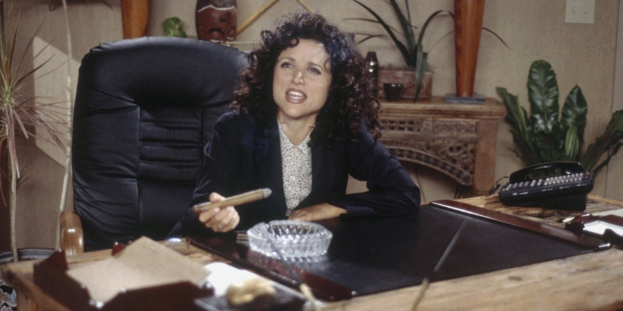 Elaine sits at a desk with a cigar