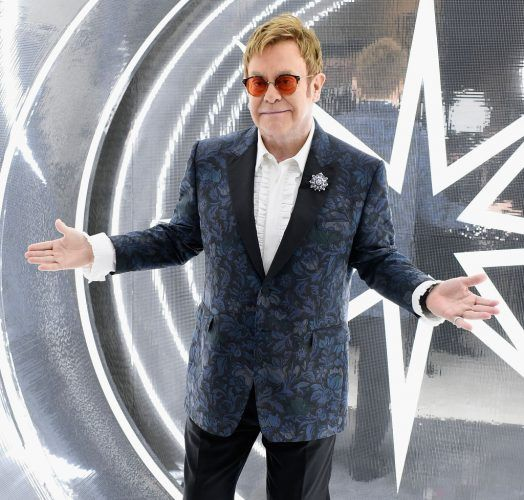 Elton John posing in front of a bright silver wall.