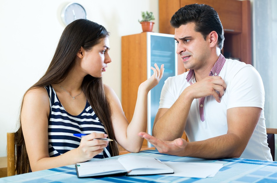 Emotional young man and woman sitting at home with notes
