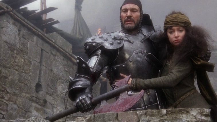 Patrick Stewart in armor holding an axe and Cherie Lunghi holding on to him in Excalibur