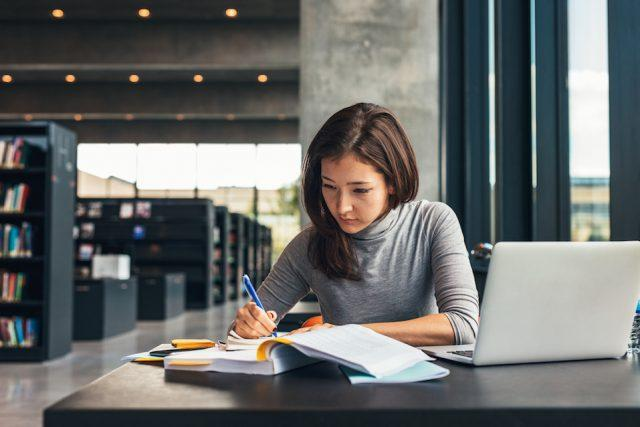 woman sitting at table doing assignments in college library