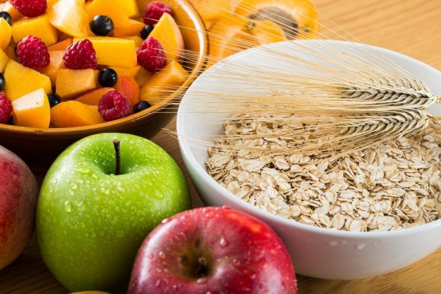 Fruit salad, apples, and oatmeal on a wooden table.