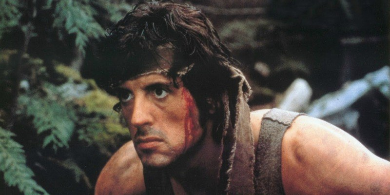Rambo has blood trickling down his face as he is going through the woods.