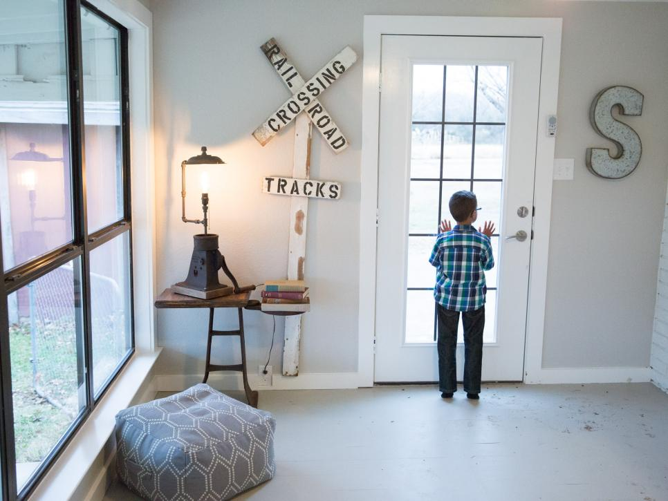 Five-year-old Julian Silva peeks into the driveway from the new side door of the family room, as seen on HGTV's Fixer Upper. Chip and Joanna Gaines rebuilt the crumbling wall and door