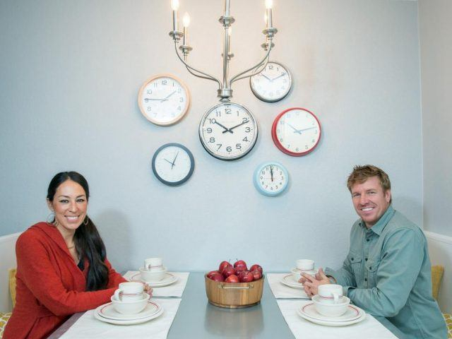 Fixer Upper hosts Chip and Joanna Gaines sit in the new kitchen built-in in the Silva home.