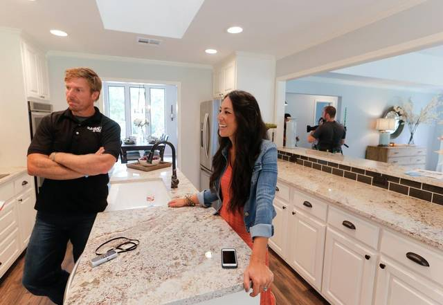 Chip and Joanna Gaines stand at a kitchen island on Season 4 of HGTV's Fixer Upper