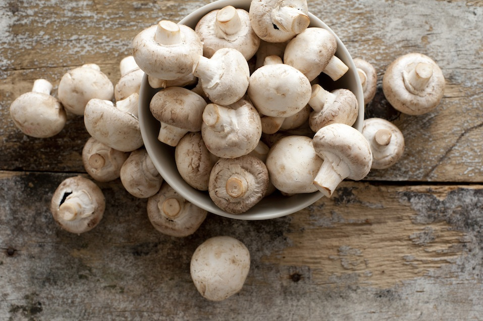 Agaricus, in a bowl on a rustic wooden counter ready to be cleaned and washed for dinner,