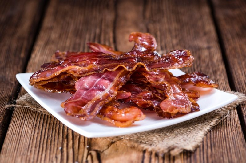 Fried Bacon (selective focus) on an old vintage wooden table