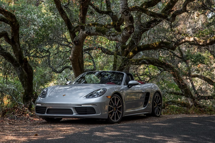 A silver Porsche 718 Boxster S with the top down