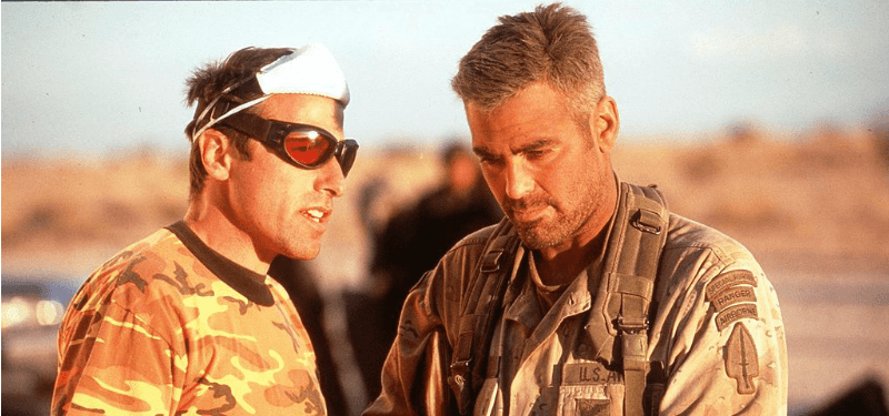 David O. Russell is talking to George Clooney who is dressed as an army man.