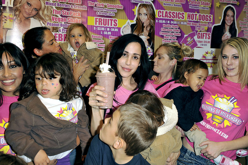 Nadya Suleman holding a milkshake, surrounded by her 14 children
