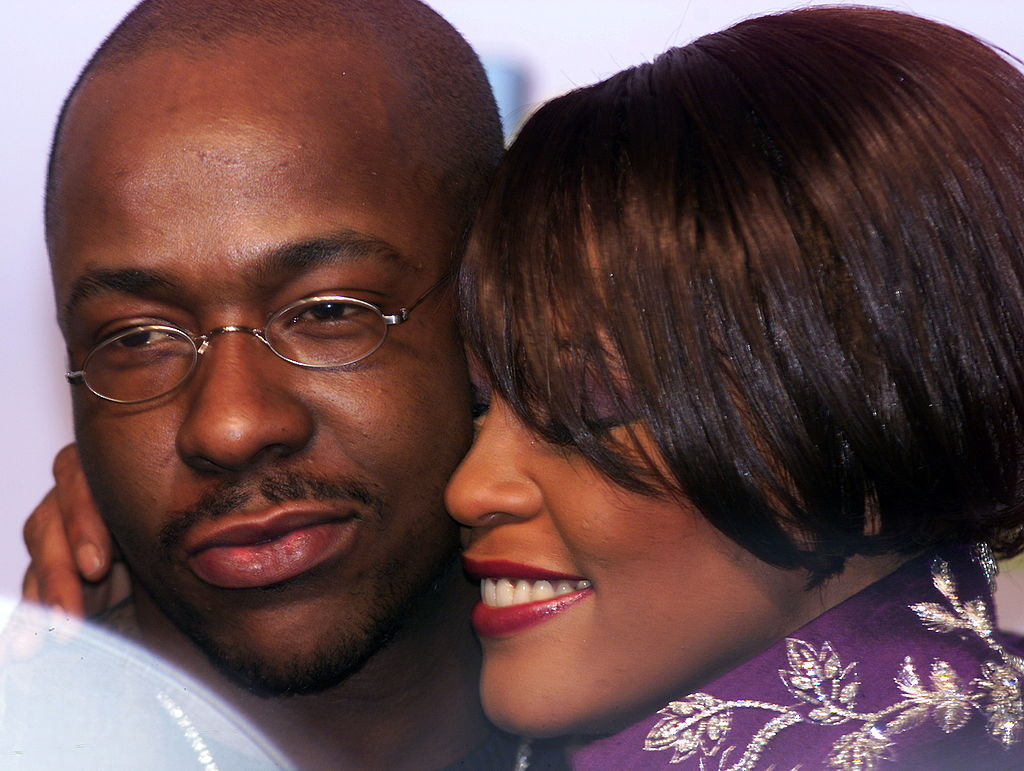 Bobby Brown wearing glasses, with Whitney Houston embracing him closely