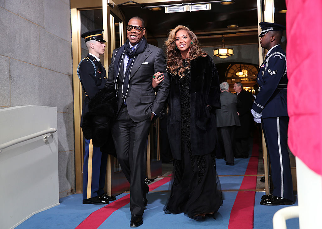 Jay-Z and Beyonce locking arms, smiling, and walking togethe