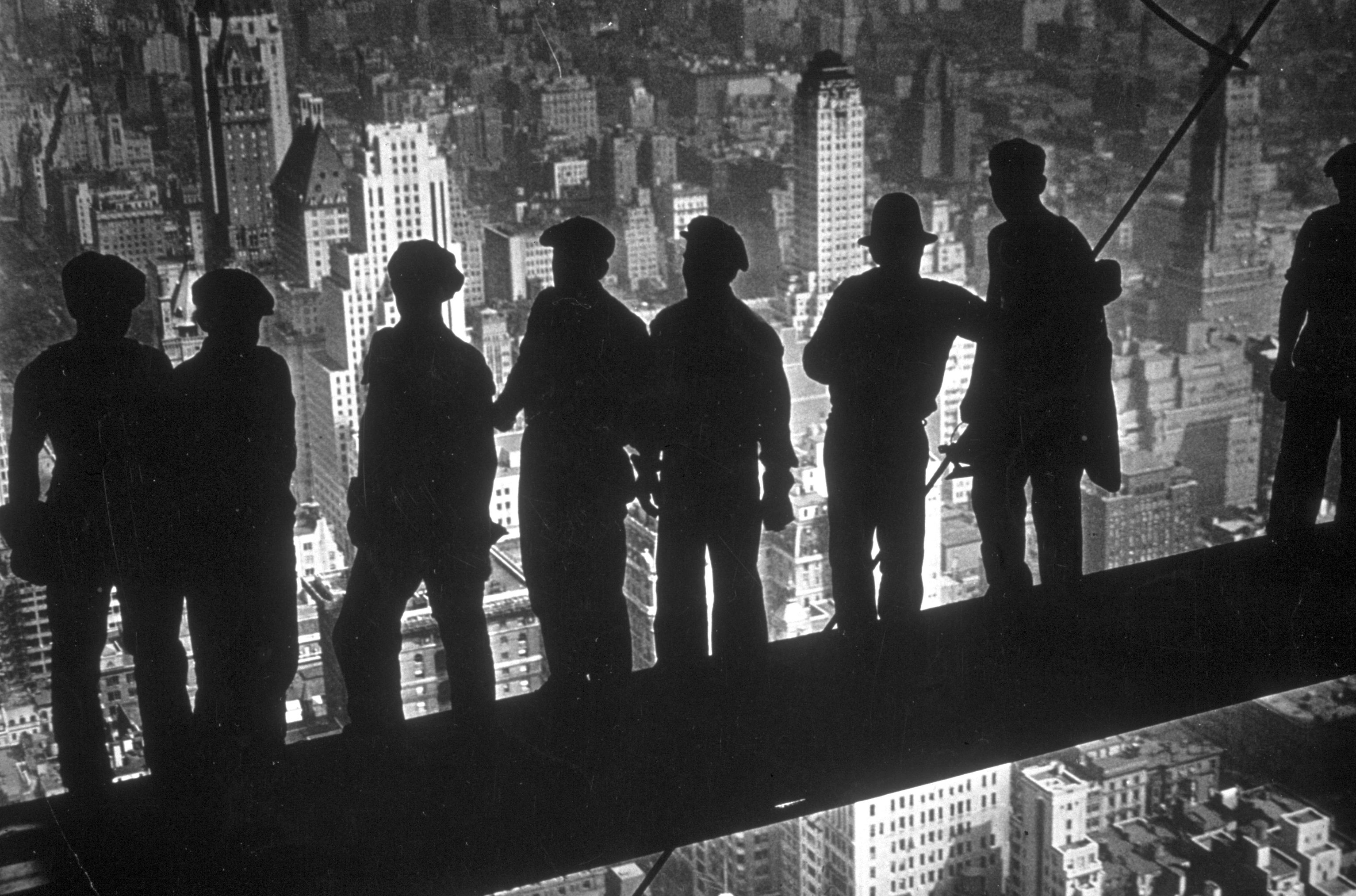 A group of steelworkers stand on scaffolding.