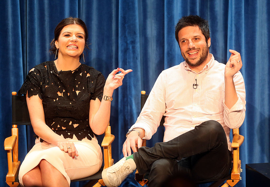 Casey Wilson and David Caspe laughing together, while speaking at a panel together in 2014