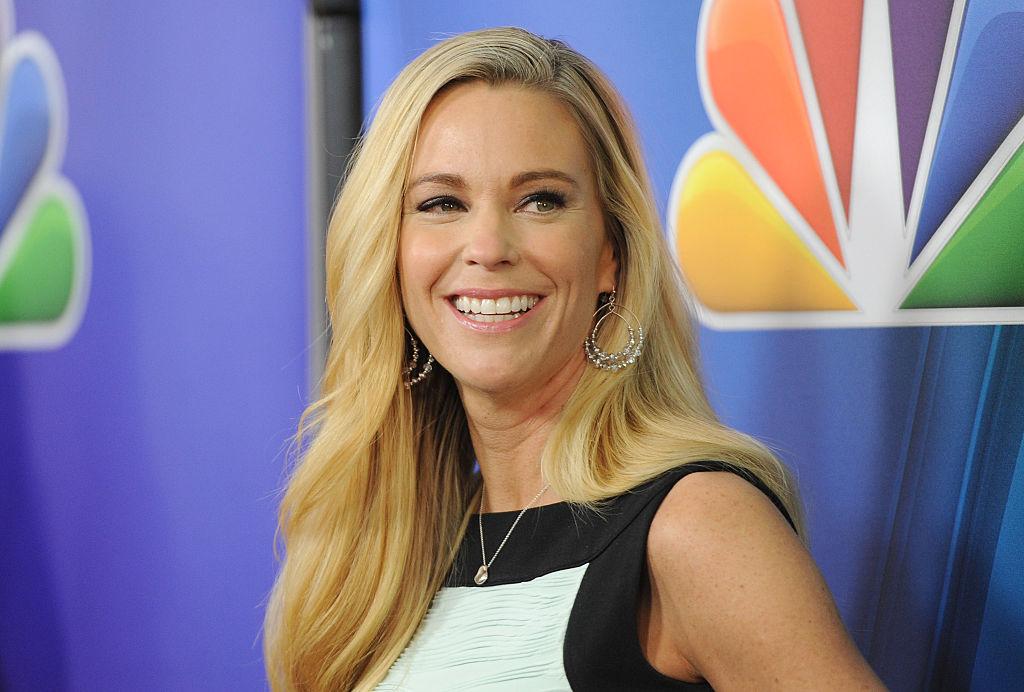 Kate Gosselin smiling, wearing a dress in front of an NBC logo