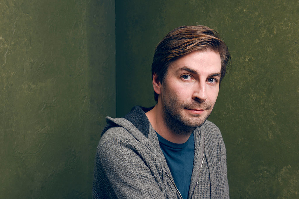 Director Jon Watts in a grey hoodie, smiling for a portrait