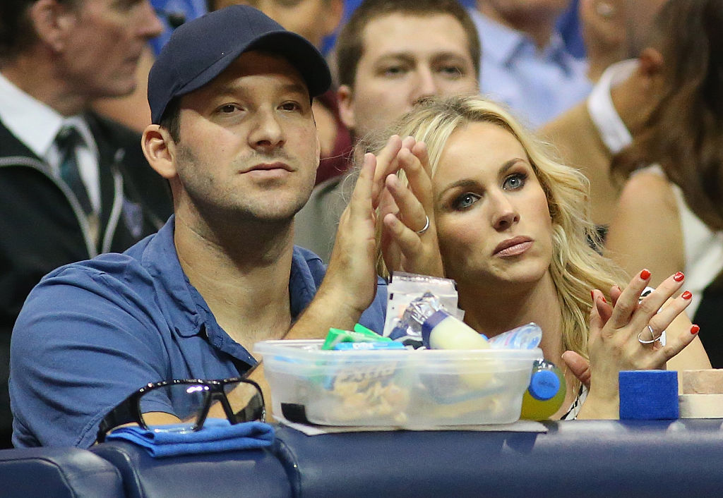 Tony and Candace Romo at a basketball came, applauding
