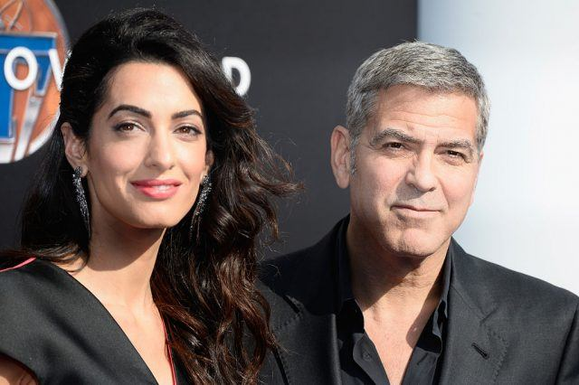 George and Amal Clooney smiling for the camera together on the red carpet.