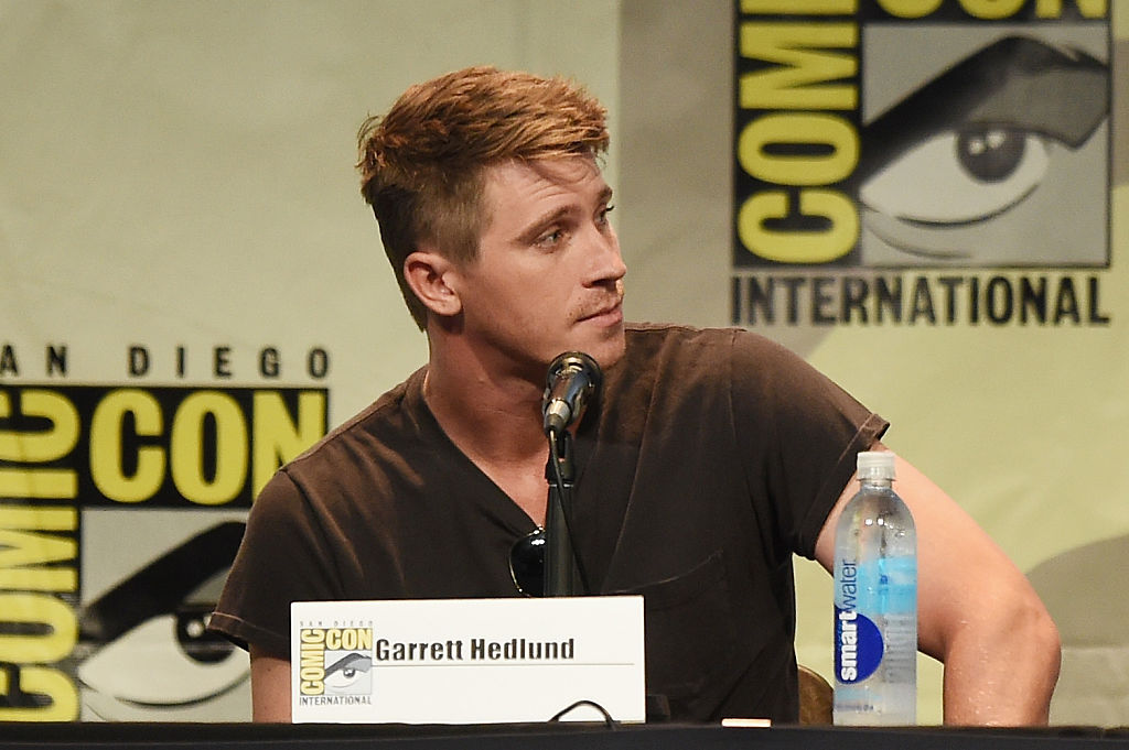 Garrett Hedlund looking to his left, speaking at a Comic-Con panel