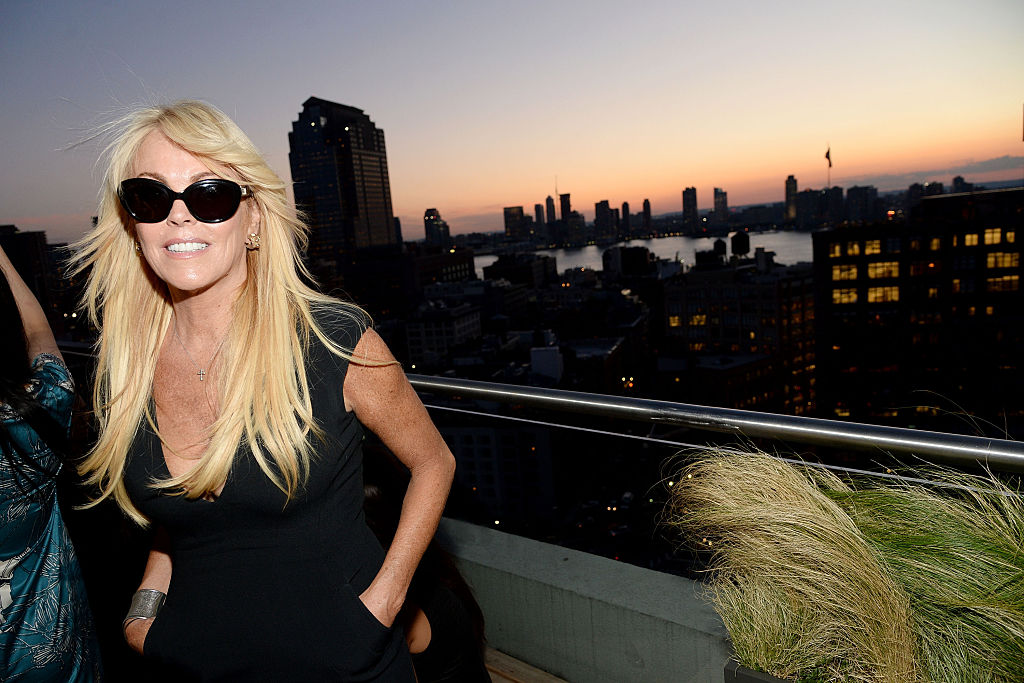 Dina Lohan smiling, in front of a sunset over a city skyline