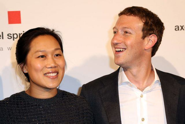 Priscilla Chan and Mark Zuckerberg smiling for the camera on the red carpet.