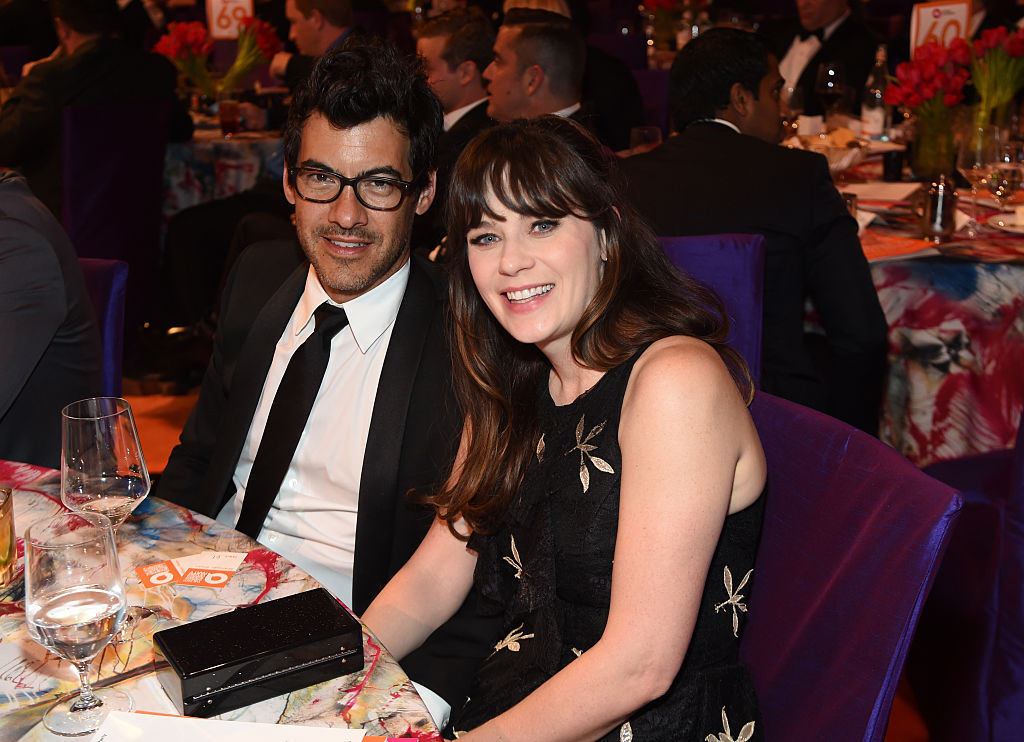 Jacob Pechenik and Zooey Deschanel smiling together, sitting at a table