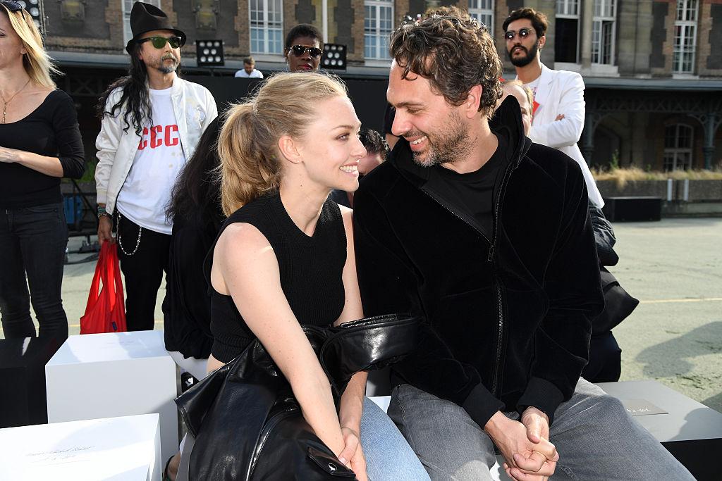 Amanda Seyfried and Thomas Sadoski sitting together at Paris Fashion Week, smiling at each other