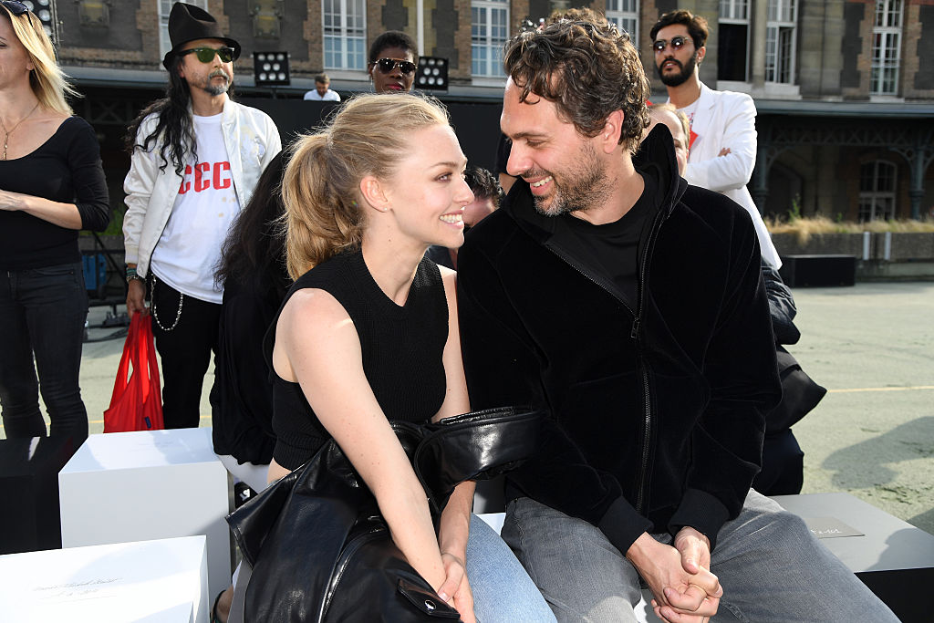 Amanda Seyfried and Thomas Sadoski sitting together at Paris Fashion Week, smiling at each other