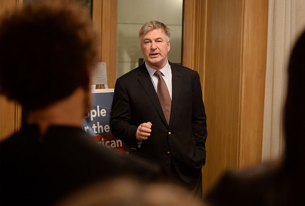 Alec Baldwin in a suit and peacoat, speaking to a crowd