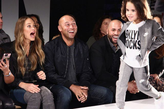 Derek Jeter and Hannah Davis smiling and laughing, while a child walks the runway at a fashion show.