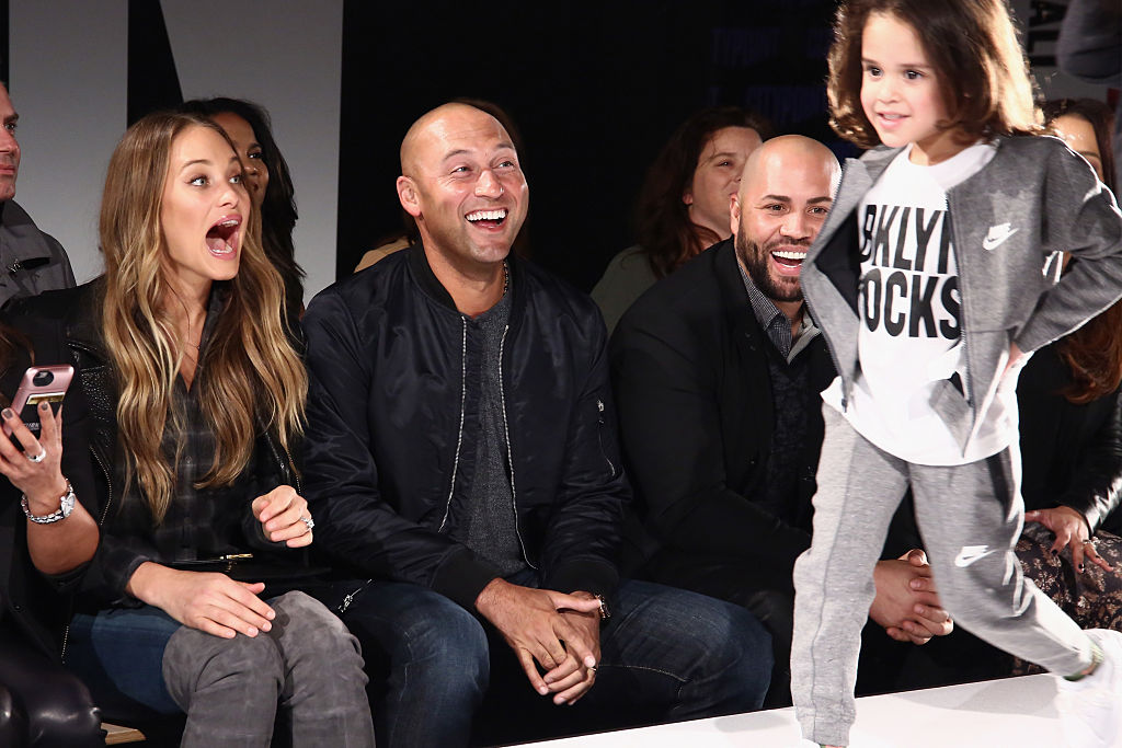 Derek Jeter and Hannah Davis smiling and laughing, while a child walks the runway at a fashion show