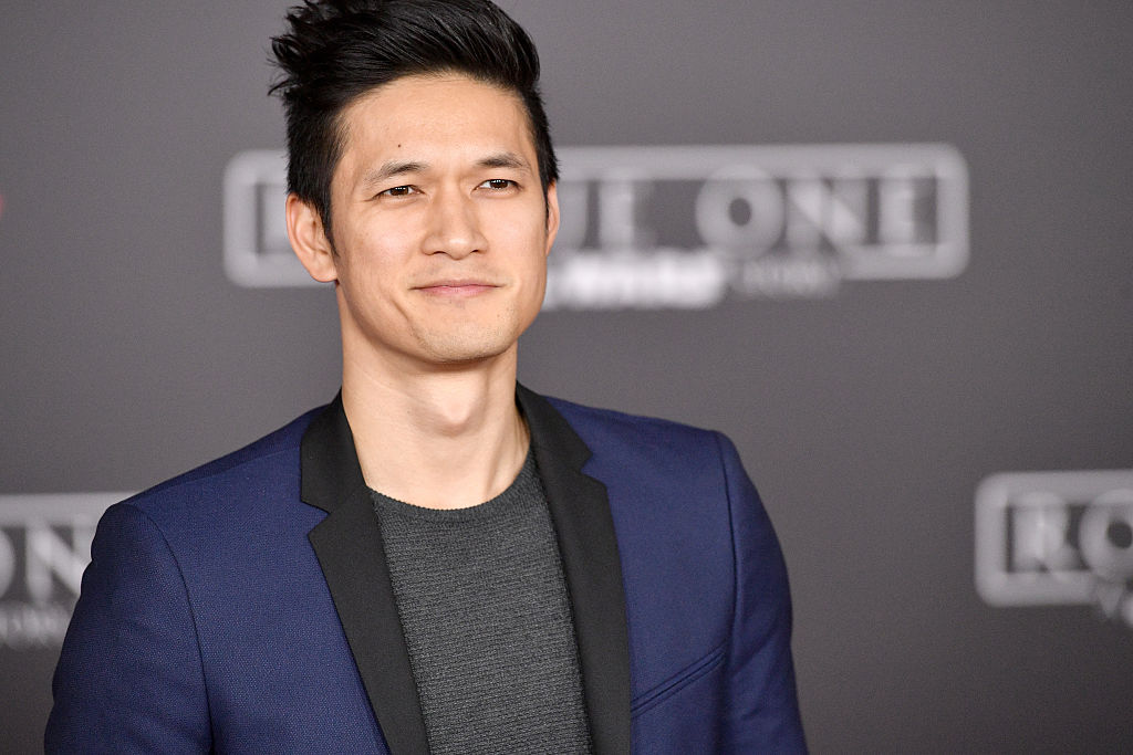 Harry Shum Jr. smiling on the red carpet at the world premiere of Rogue One