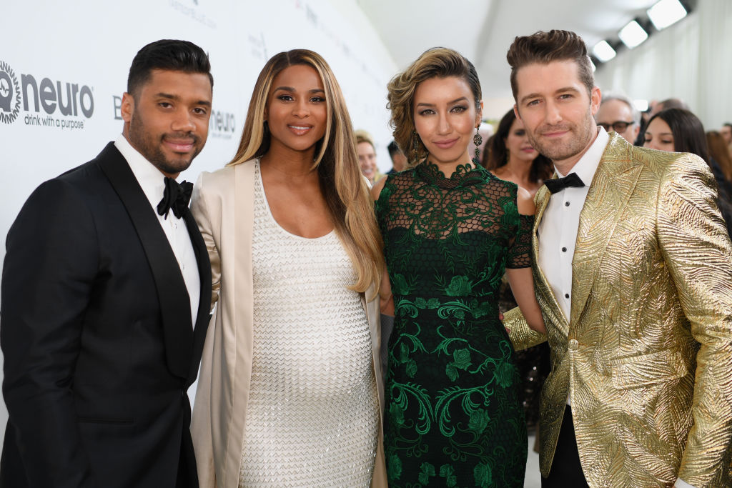 Russell Wilson, smiling next to a pregnant Ciara on the red carpet
