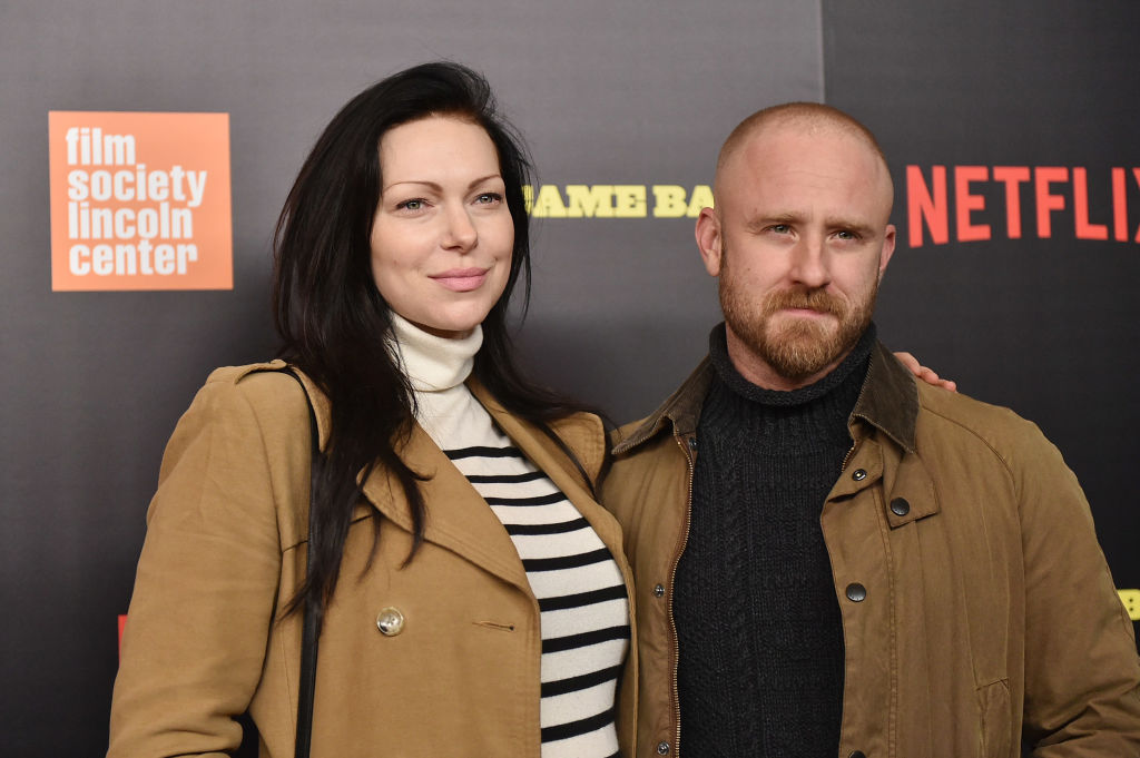 Laura Prepon and Ben Foster smiling on the red carpet together for a Netflix premiere