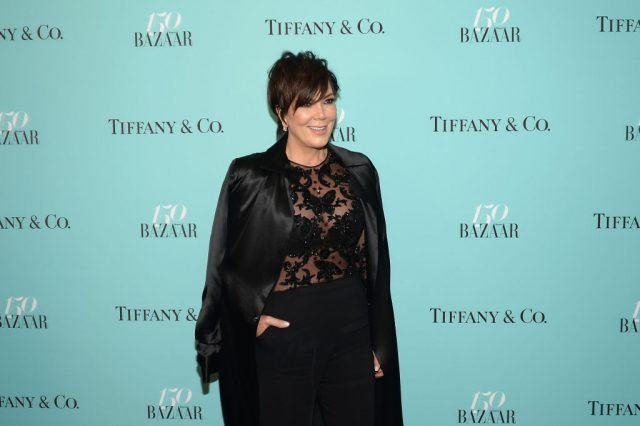 Kris Jenner wearing a black dress and smiling on the red carpet.
