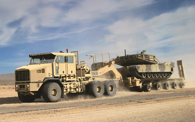A Global Heavy Equipment Transporter towing a tank across the sand.