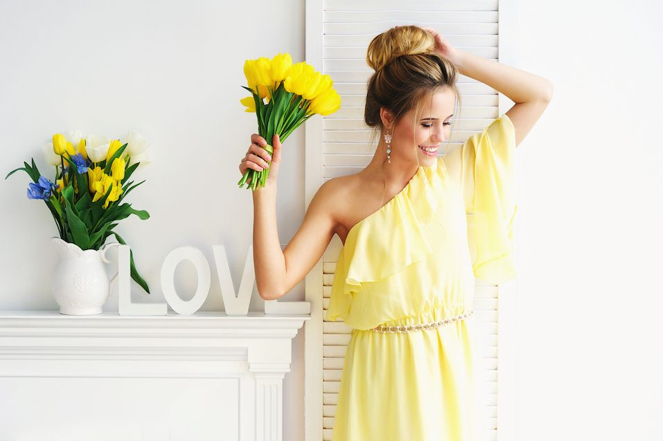 Portrait of a young woman in yellow dress with spring flowers and white decoration letters
