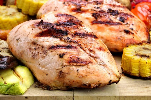 White meat grilled chicken and veggies on a table.