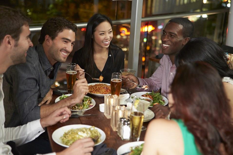 Friends Enjoying Evening Meal In Restaurant