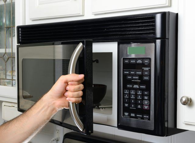 A person opening a microwave door.