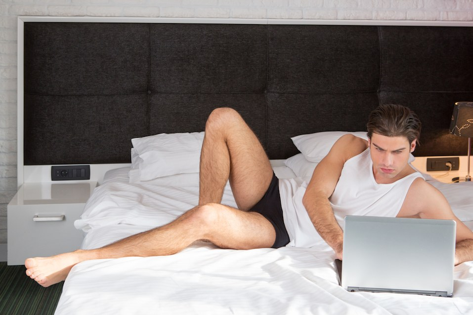 man on hotel bed on computer