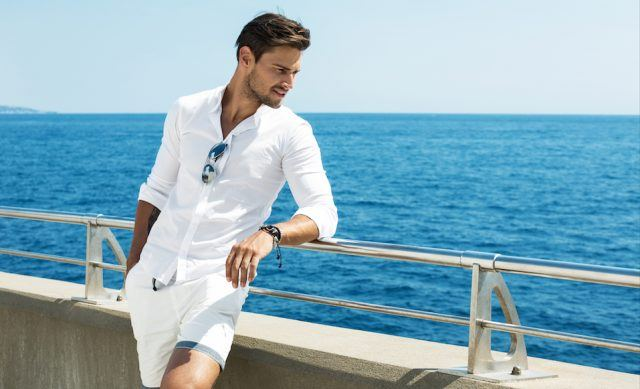 Man wearing white clothes posing in sea scenery