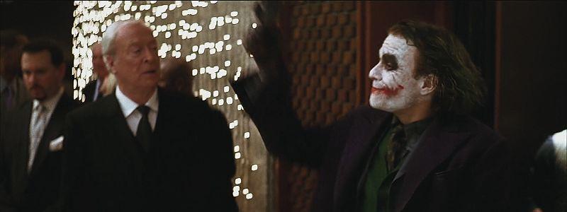 Heath Ledger holding a gun in the air as The Joker