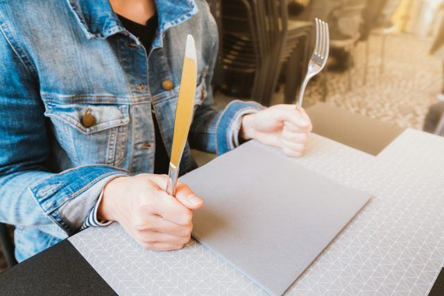 Hungry woman holding a knife and a fork while at a restaurant