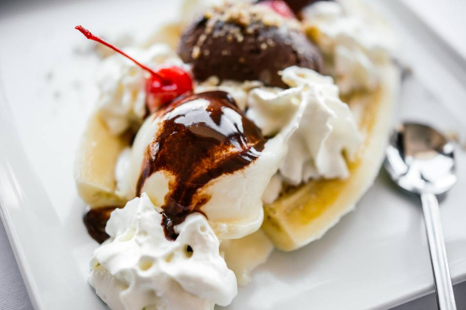 Banana split ice cream served on white plate